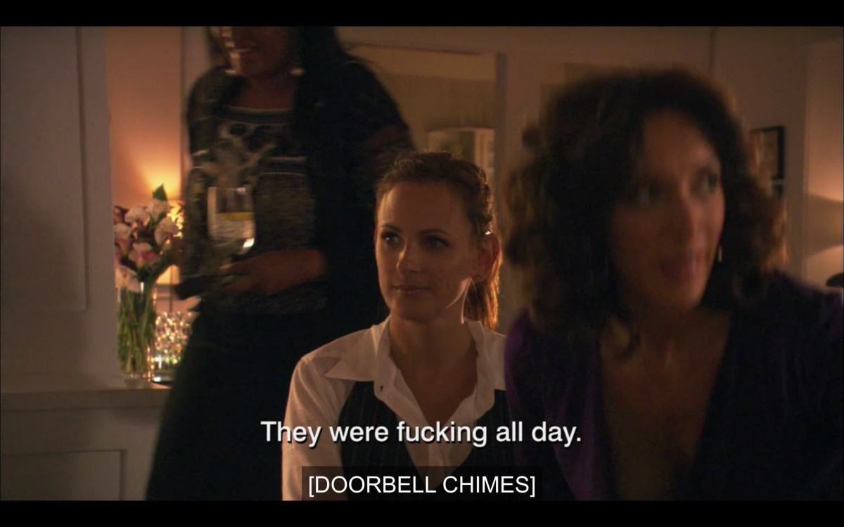 "Jodi and Bette sitting together on a couch. Subtitles read, ""They were fucking all day. [Doorbell chimes]"""
