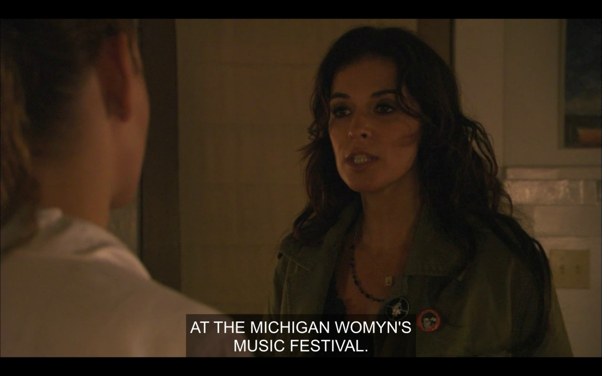 "Kate, with long brown hair and wearing a forest green jacket, says, ""At the Michigan Womyn's Music Festival."""