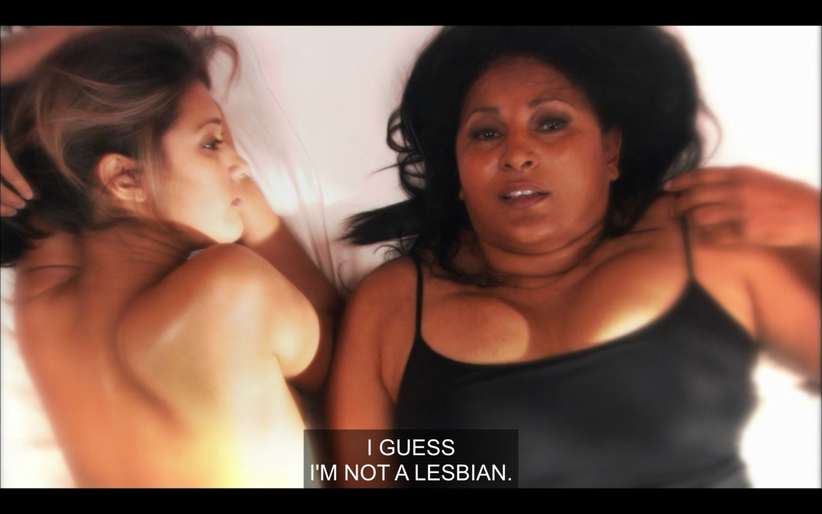 """Papi (topless) and Kit (wearing a black tank top) lay next to each other in a bed with white sheets. Kit stares up at the ceiling and says, """"I guess I'm not a lesbian."""""""