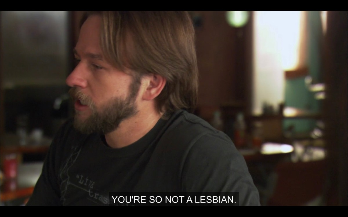 """Angus (in a black t-shirt) sits at The Planet. He says, """"You're so not a lesbian."""""""