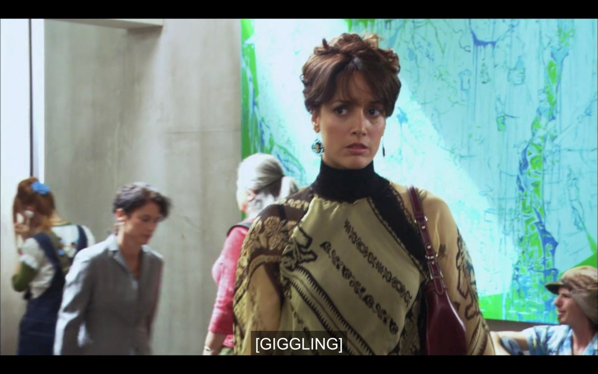 """Bette standing in front of a blue-and-green mural at an art show opening. Her hair is pinned up and she's wearing a tan and black high-collar dress. Subtitles read, """"[Giggling]"""""""
