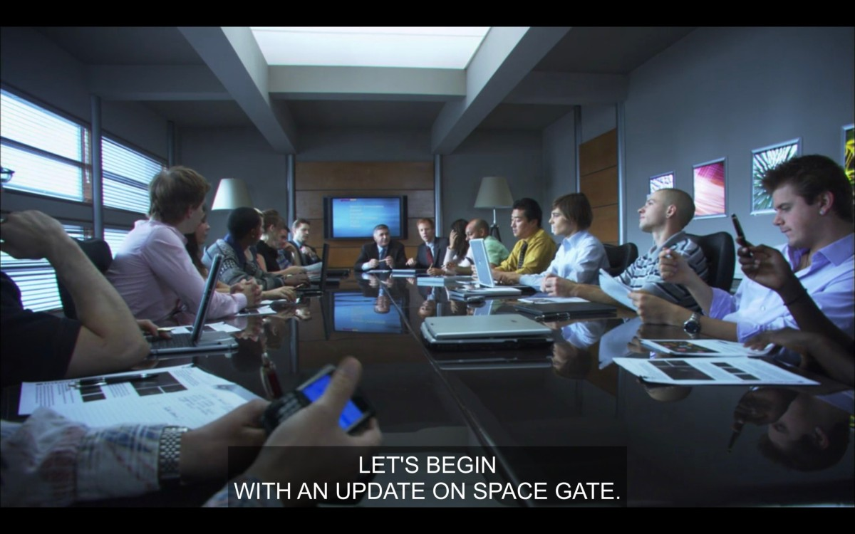 """A big long conference table, with Max surrounded by a bunch of other tech dudes on their phones and laptops. His boss, at the head of the table, says, """"Let's begin with an update on space gate."""""""