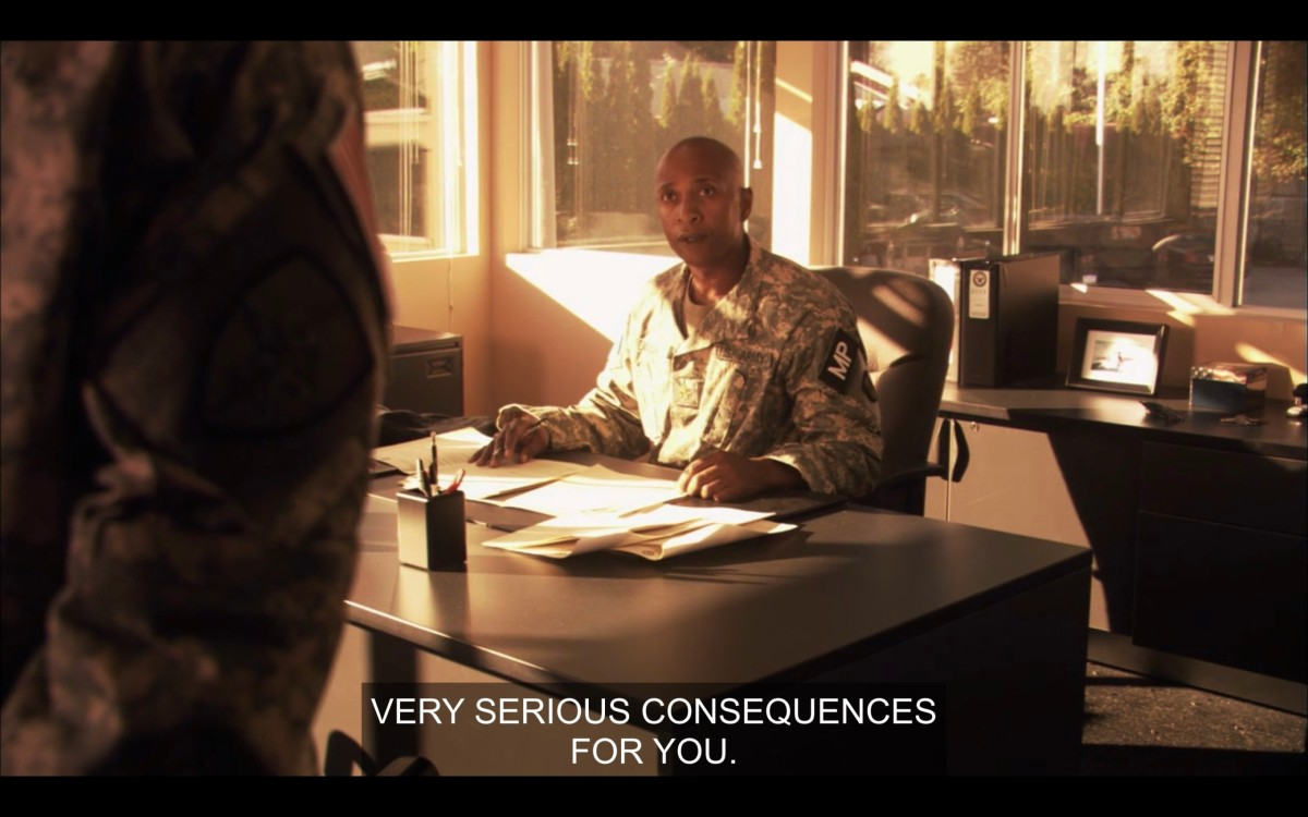 """A bald person wearing an army uniform and sitting at a desk. Slightly off camera, Tasha stands in front of the desk with her hands behind her back. The army official says, """"Very serious consequences for you."""""""