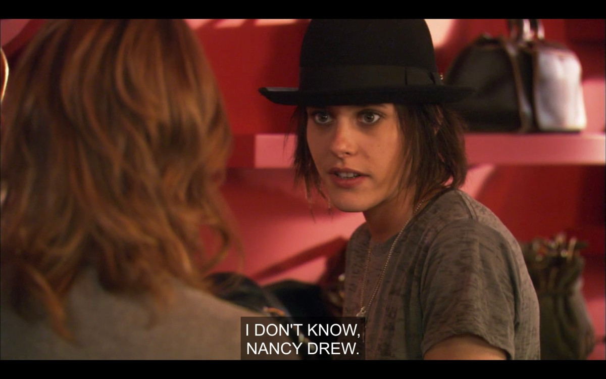 """Shane (wearing a grey t-shirt and a black fedora) and Alice (back to the camera) at a shoe store. Shane says, """"I don't know, Nancy Drew."""""""