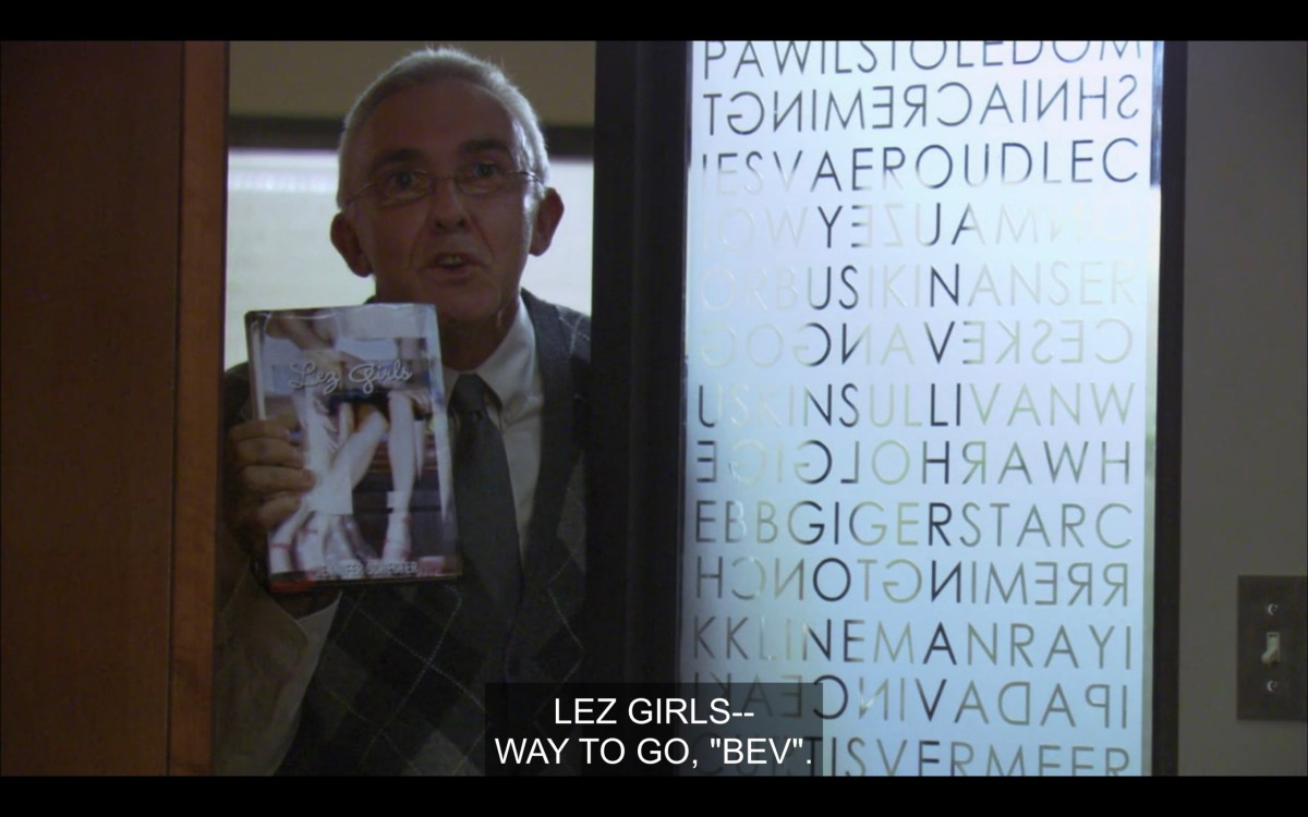 """An old guy in a full suit and tiny glasses holds a copy of Les Girls up to the window looking into Bette's office. He says, """"Lez Girls -- Way to go, 'Bev.'"""""""
