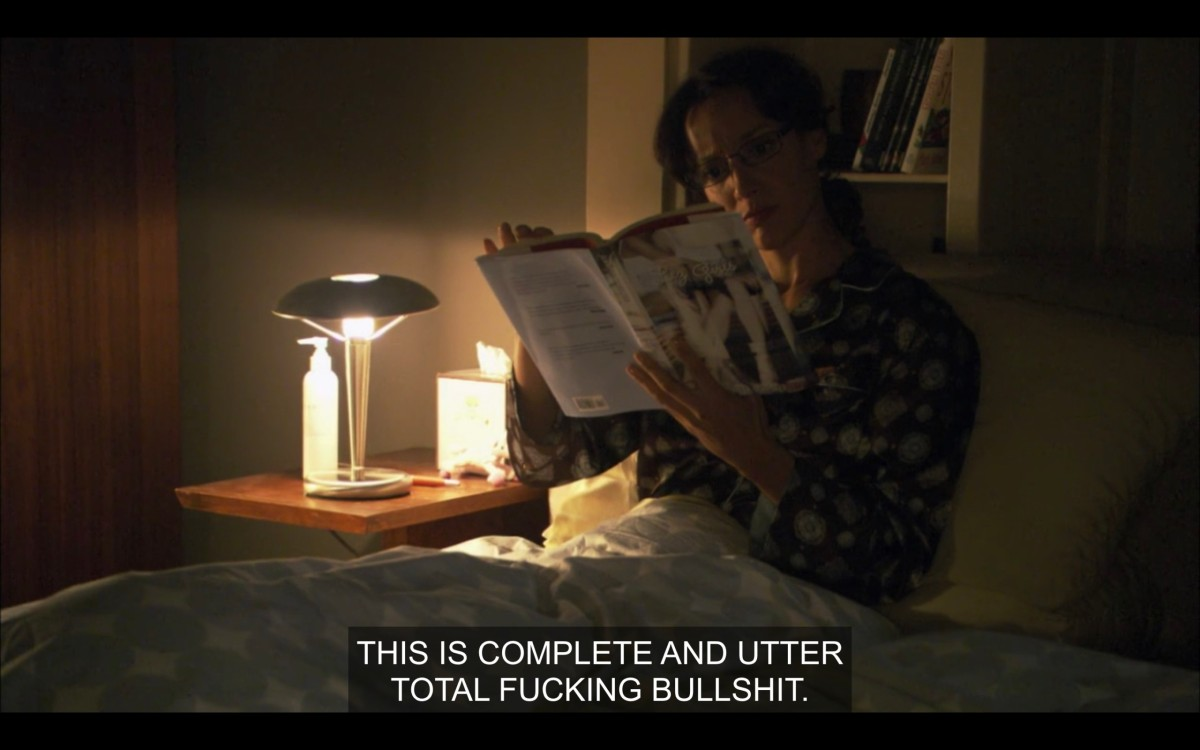 """Bette sitting up in bed, reading Lez Girls. She says, """"This is complete and utter total fucking bullshit."""""""