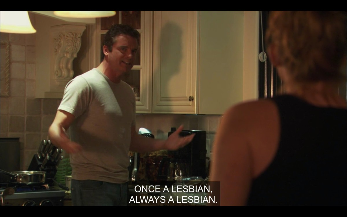"""Henry and Tina (her back to the camera) standing in the kitchen. Henry says, """"Once a lesbian, always a lesbian."""""""