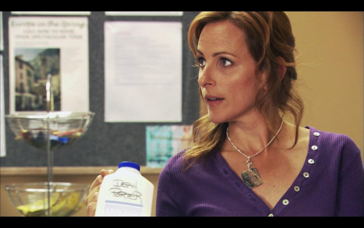 "Jodi, wearing a purple henley shirt, holds up a half-gallon jug of 2% milk with ""Dean Porter"" written on it in Sharpie."