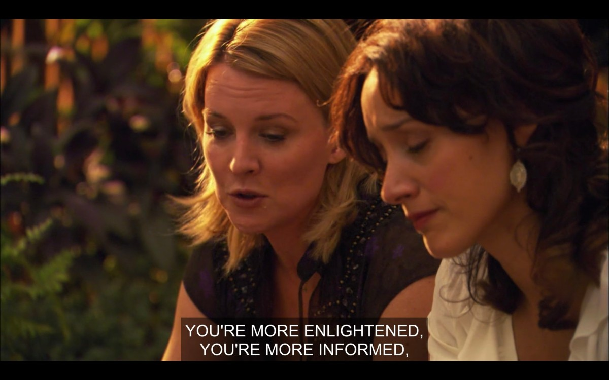 """Tina (wearing a black top) and Bette (wearing a white top) sit outside next to each other. Tina says, """"You're more enlightened, you're more informed,"""""""
