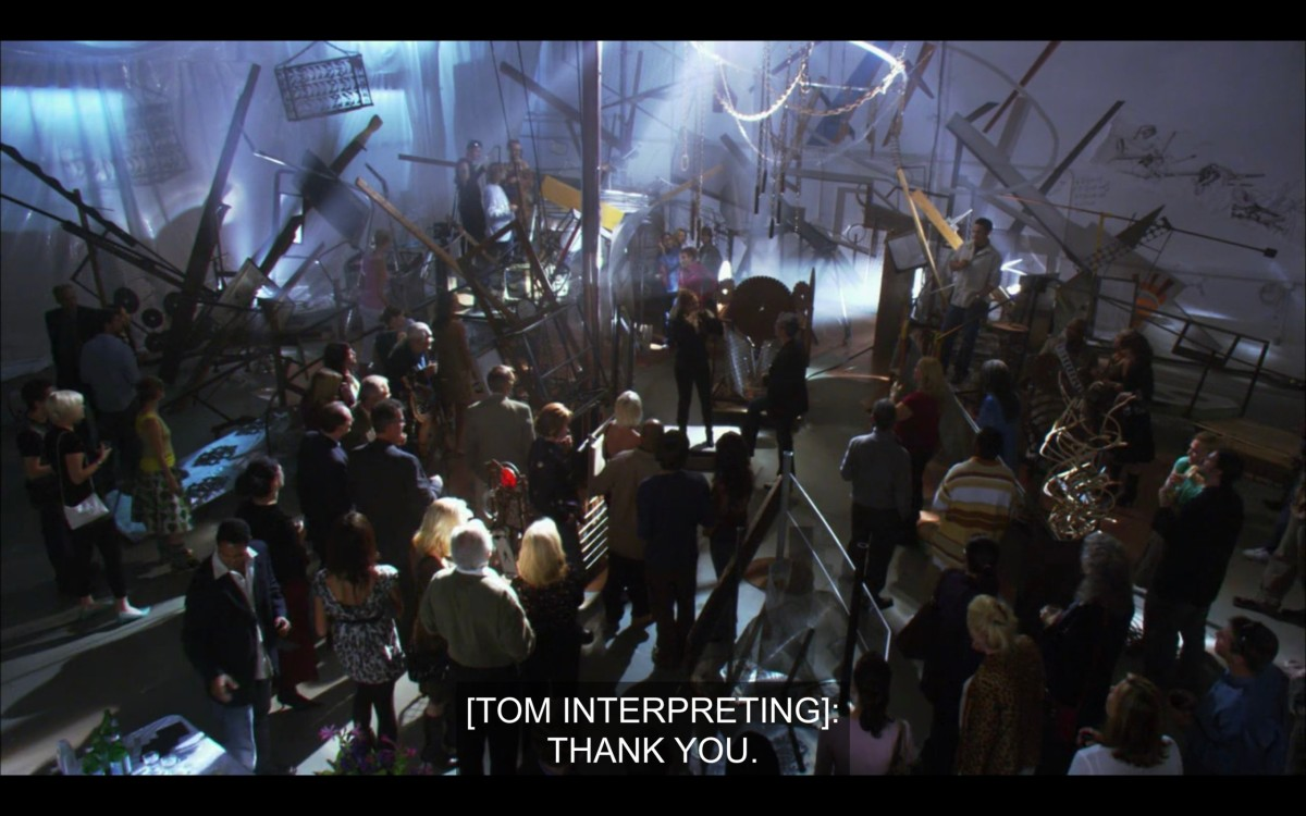 """Overhead shot of a crowded room at Jodi's art show. Subtitles read, """"[Tom interpreting]: Thank you."""""""