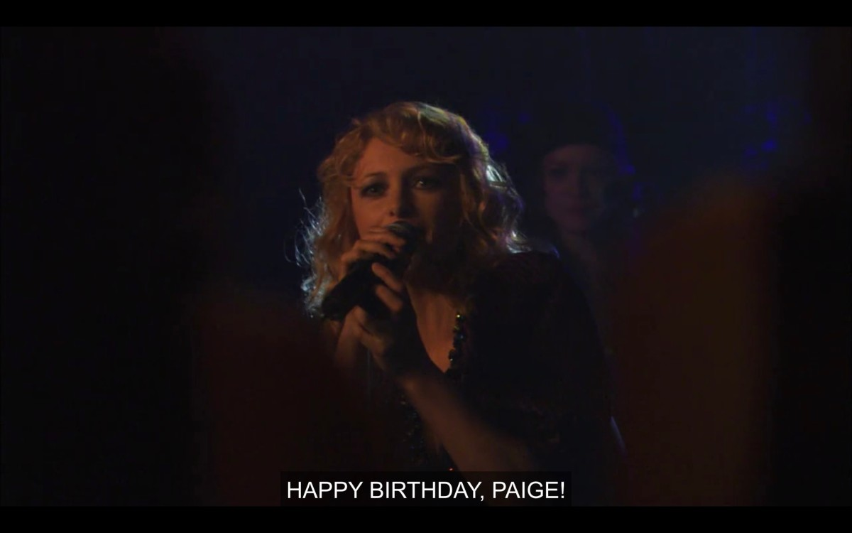 """A blonde singer in a dark room holding a microphone. She says, """"Happy birthday, Paige!"""""""
