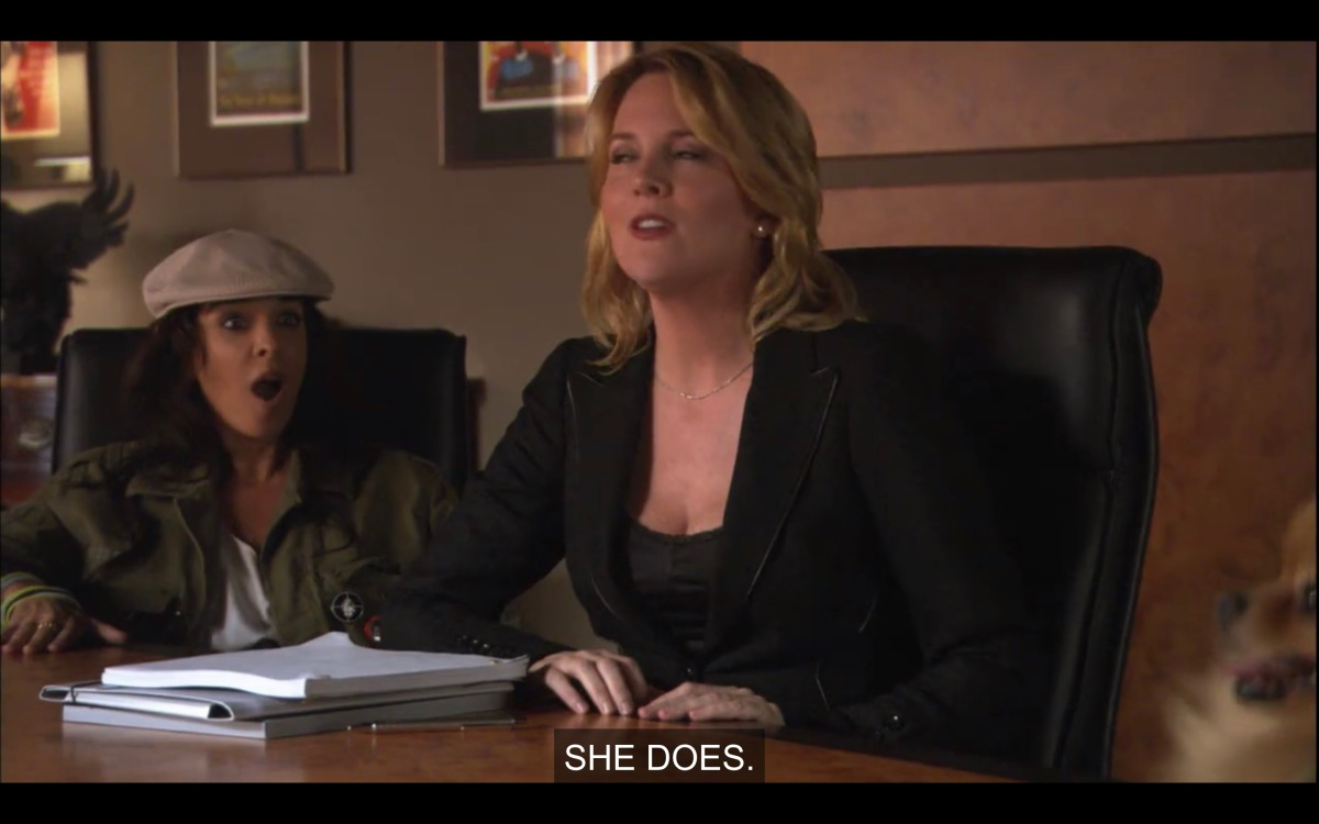 "Tina (in a black suit) sits at a conference table in front of a stack of white papers. There's a brunette woman in a tan cap sitting next to her with her mouth wide open. Tina says, ""She does."""
