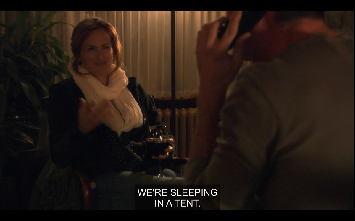 "Dimly-lit shot of Jodi, holding a glass of red wine and wearing a big white scarf. Bette sits across from her, her back to the camera. Jodi says, ""We're sleeping in a tent."""