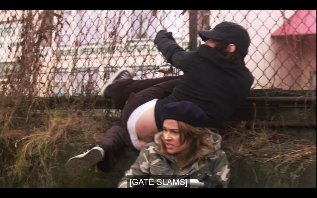 "Alice (wearing a black beret and an camouflage jacket) and Shane (wearing all black, her pants falling down slightly) have just hopped a chain link fence and are now on the ground. Subtitles read, ""[Gate slams]"""