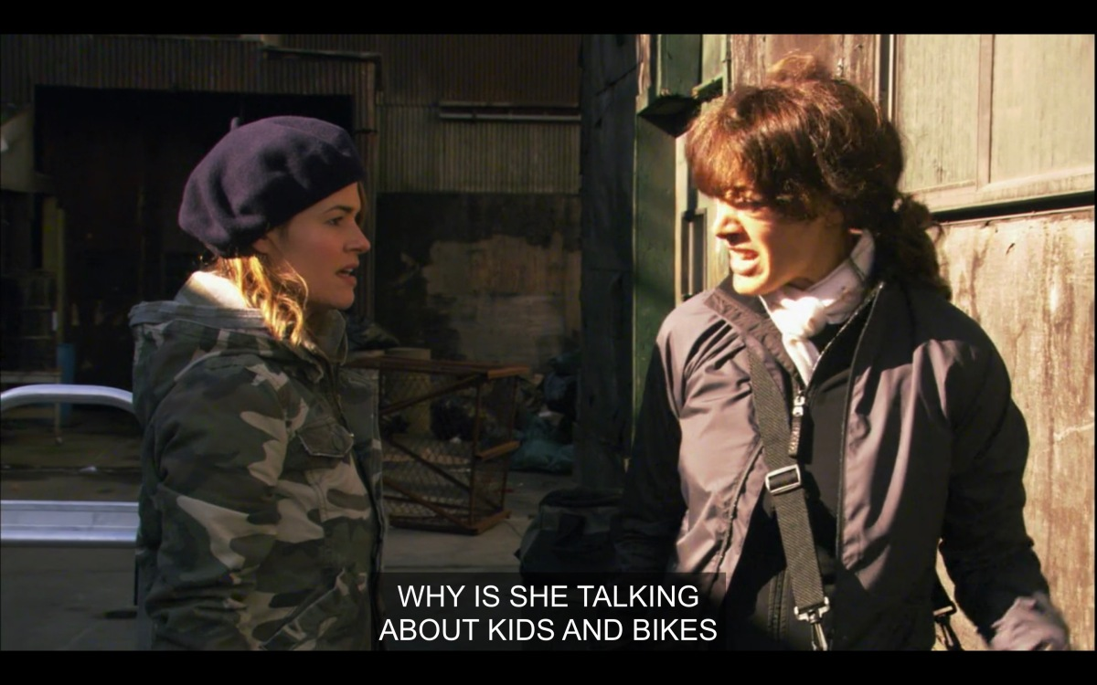 "Alice (in a black beret and a camo jacket) and Bette (wearing a black jacket and a black messenger bag across her body) facing each other outside. ""Why is she talking about kids and bikes?"""
