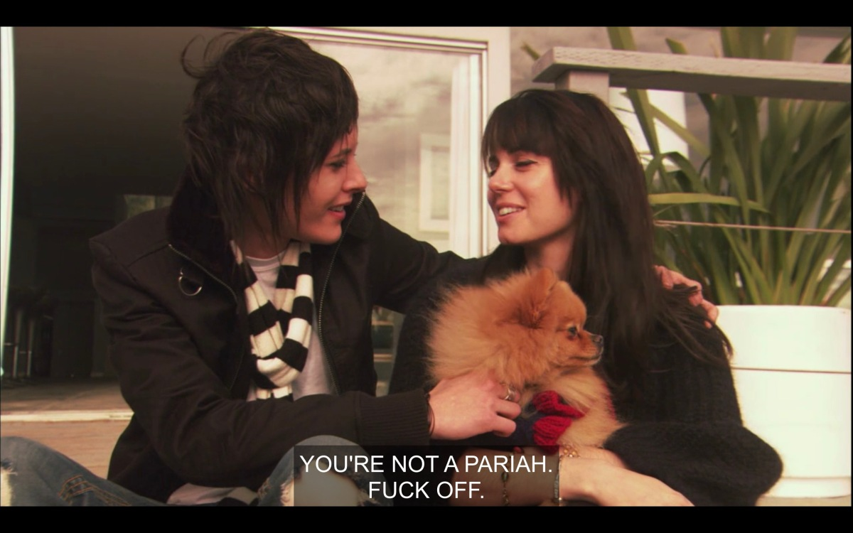 "Shane and Jenny (holding a tan Pomeranian dog) sit next to each other outside. Shane has one arm on jenny's shoulder, the other hand on the dog. They are looking and smiling at each other. Shane says, ""You're not a pariah, fuck off."""