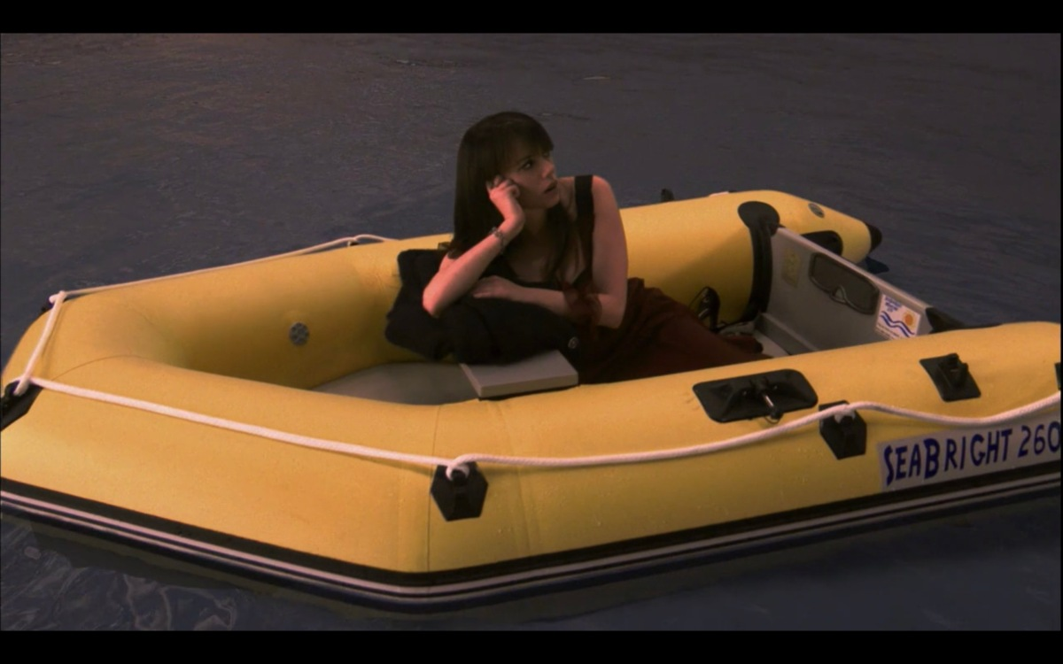 Jenny sits alone in an inflatable yellow boat in the water, resting her head in her hands.