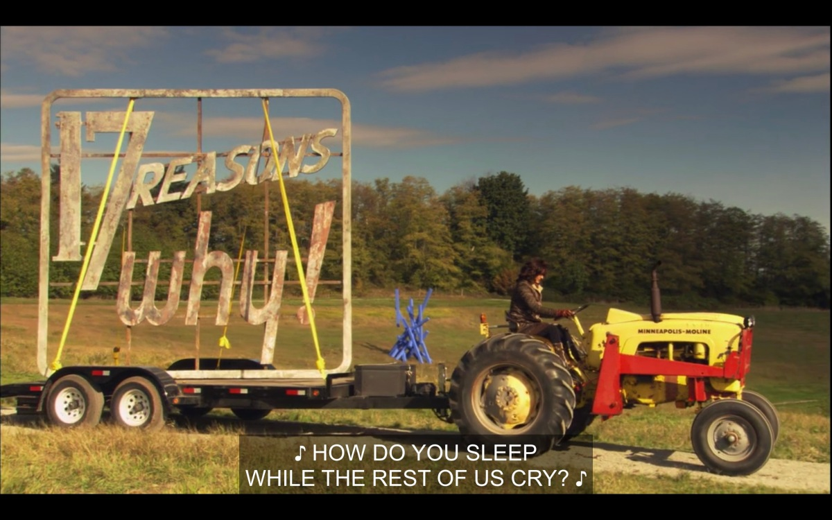"Bette is driving an enormous yellow tractor, with a trailer attached carrying the ""17 reasons why!"" billboard that they stole. Music plays in the background, singing, ""How do you sleep while the rest of us cry?"""