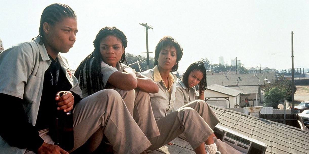 A scene from Set It Off where the four main characters of set it off sitting on a roof overlooking a factory