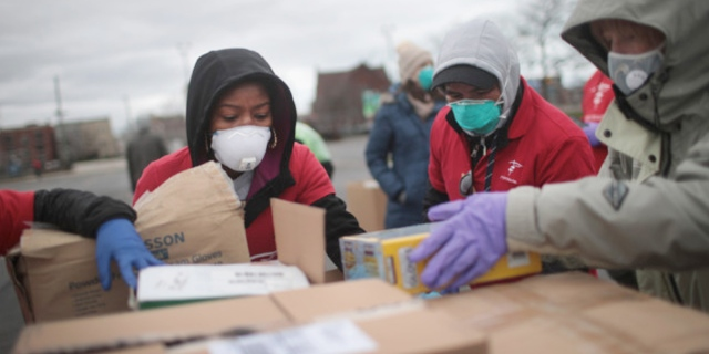 relief workers in masks helping unload boxes