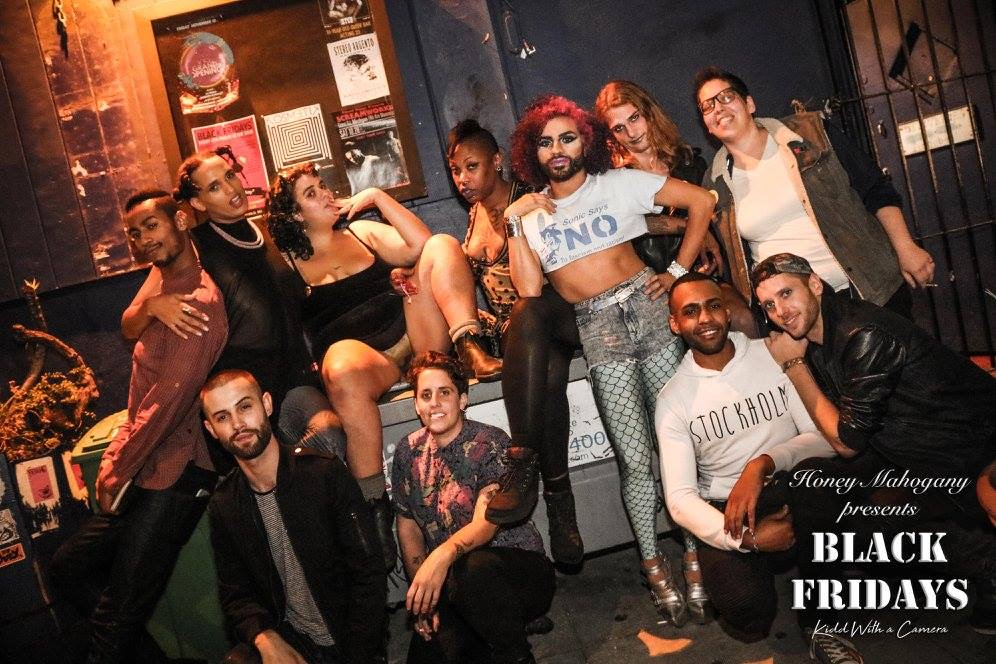 11 queer folks pose for the camera in two rows outside a bar at night; their arms are thrown around each other and they look comfortable with each other. The bottom right corner reads Honey Mahogany Presents Black Fridays.