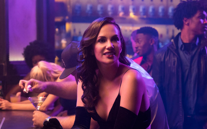 A white woman with long, brown hair sits at a bar in a black dress and black, elbow-length gloves
