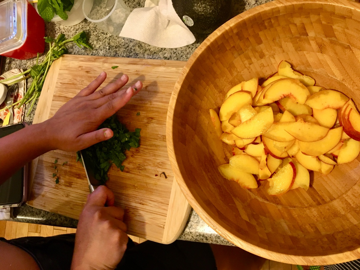 hands chopping herbs beside bowl of peaches