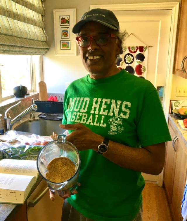 front shot of my dad, a south indian man in a baseball cap and bright green t-shirt that says Mud Hens baseball on it, holding up a finished batch of gunpowder in the blender