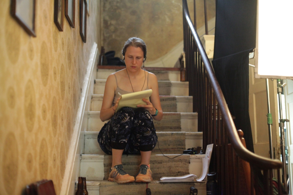 A candid photo of director Josephine Decker taking notes seated on a staircase on set