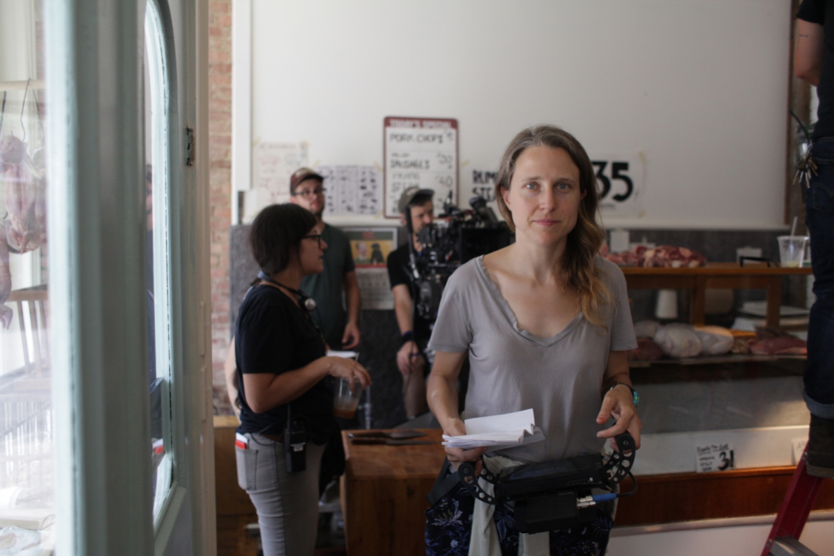 A candid photo of director Josephine Decker facing the camera on set, holding a script in hand