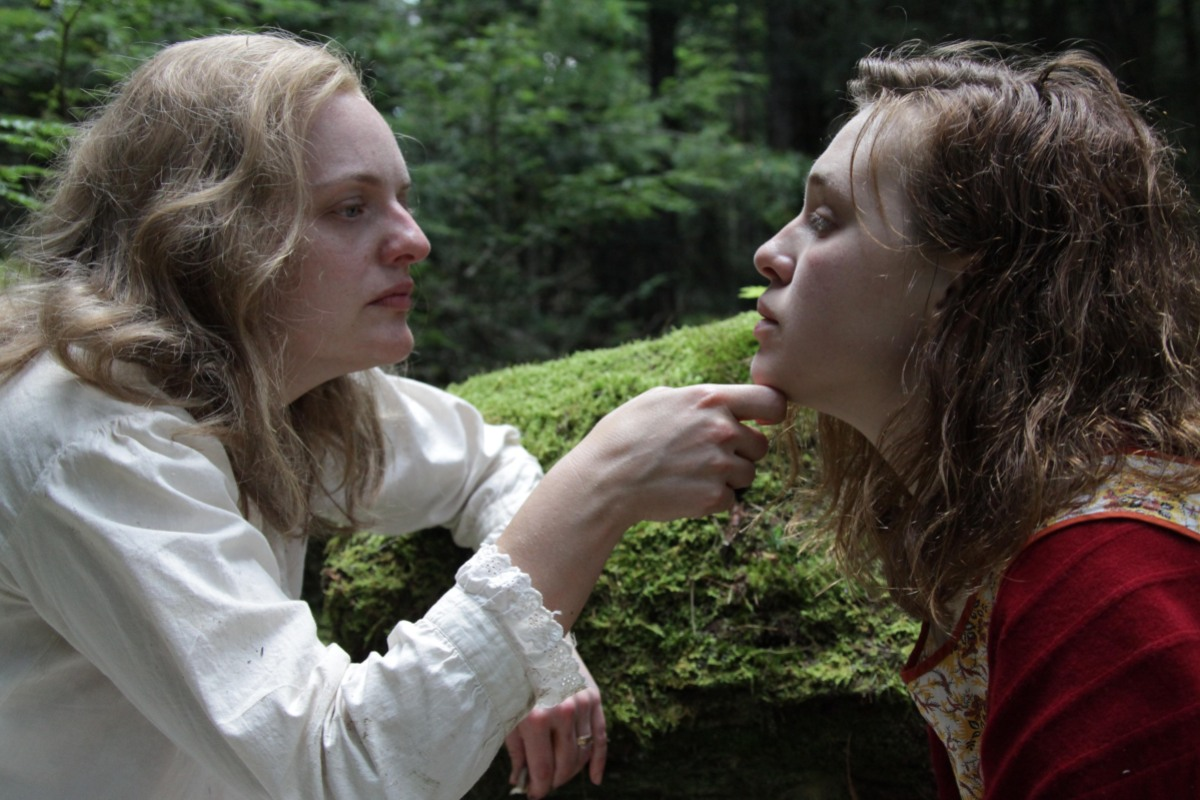 A film still from Shirley in which Elisabeth Moss's character cups the face of Odessa Young's character, who looks vulnerable and distraught