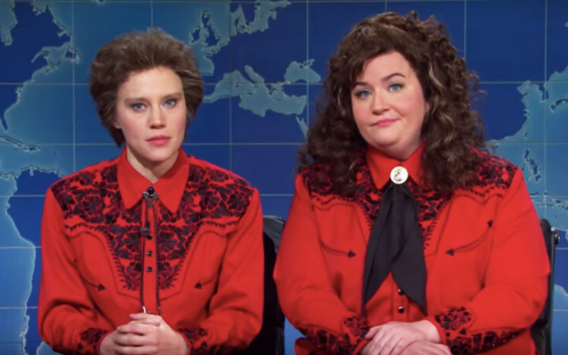 Two white women in curly hair and red western shirts sit at a news desk.