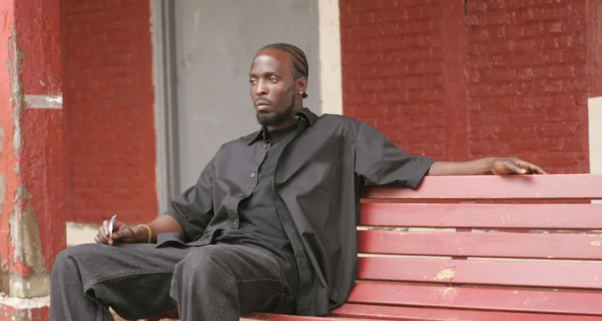 Omar LIttle sits on a red bench in front of a red brick building, wearing all black.