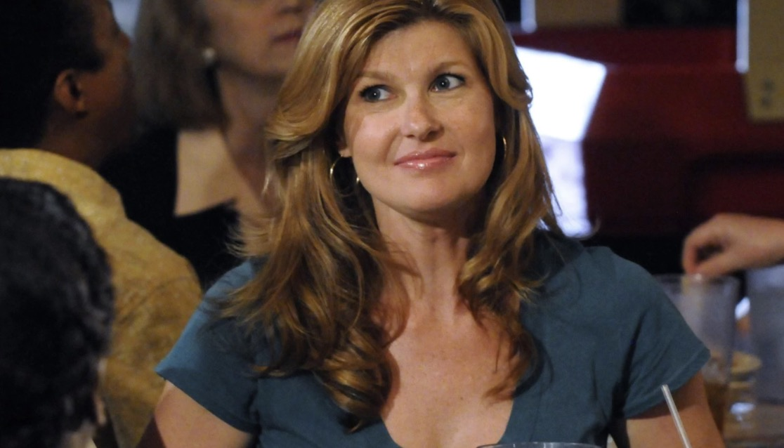 Tami Taylor in a teal v-neck at what looks like a team celebration at a bar