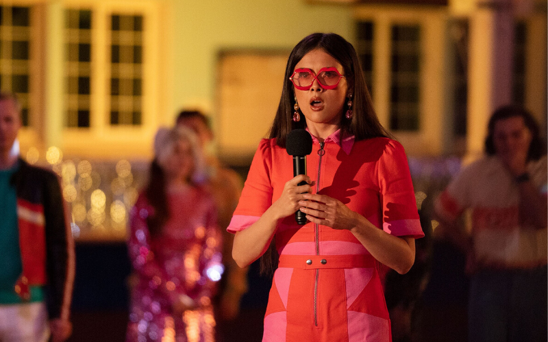 A woman with long brown hair wears a bright pink dress and pink glasses and holds a microphone