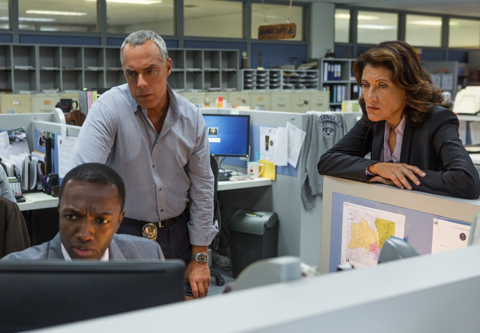 Three detectives in the office looking at a screen together, one of them is Bullets, the closeted lesbian boss of Bosch