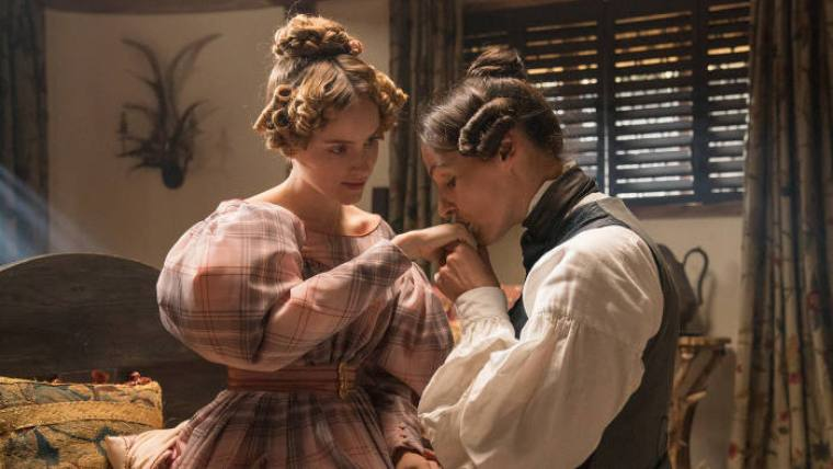 """Anne Lister kisses her girlfriend Anne on her hand in period costumes. Still from """"Gentleman Jack"""" on HBO"""