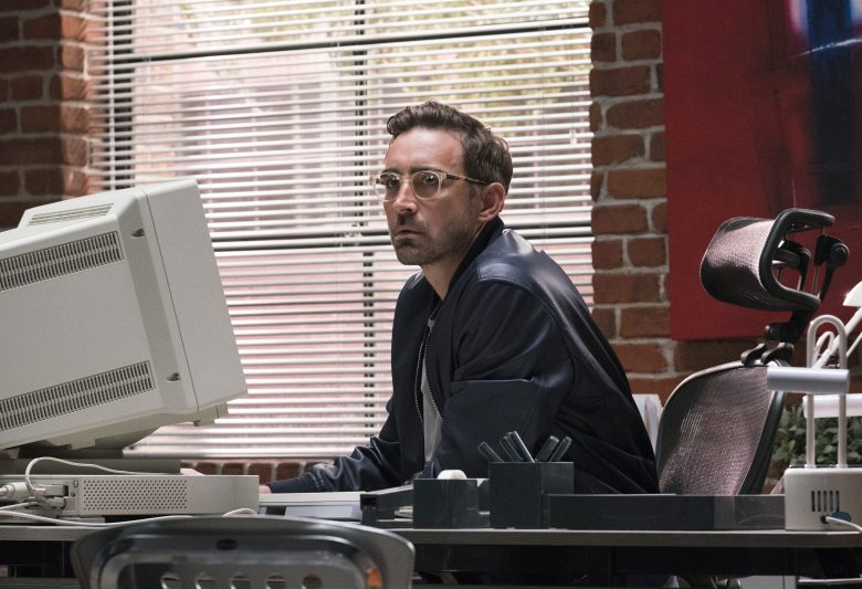 Joe MacMillion sits at a desk in front of a large computer, in the 90s. He's wearing a leather jacket and glasses. The walls are exposed brick, it's the big loft office space.