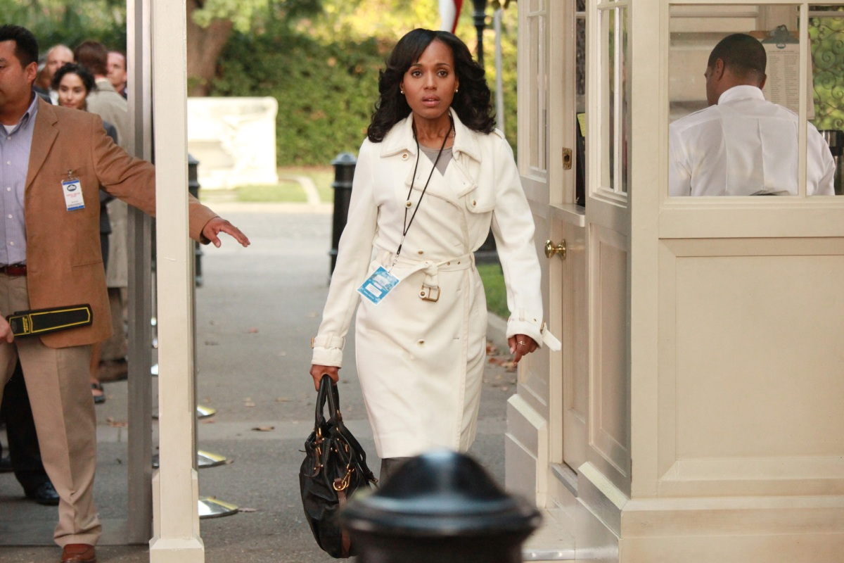 Olivia Pope is wearing a hot white trenchcoat situation and walking past a guarded gate. She's walking quickly with some kind of pass around her neck. She looks very hot and busy.