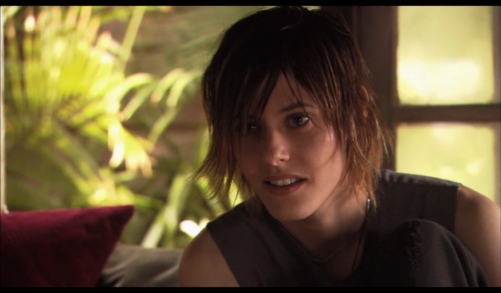 Image: Shane, a lesbian in a muscle tee with a very 2007 haircut, looks at somebody who is out of frame. The L Word.