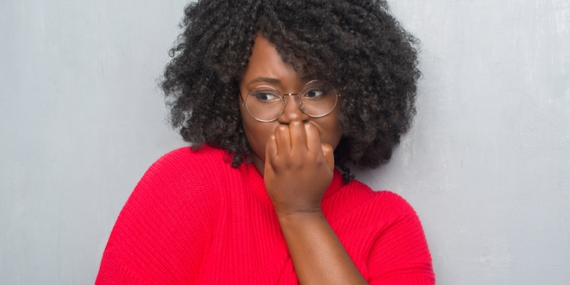 A worried-looking Black woman with natural hair and glasses looking off to the side while she holds her hand to her mouth pensively.