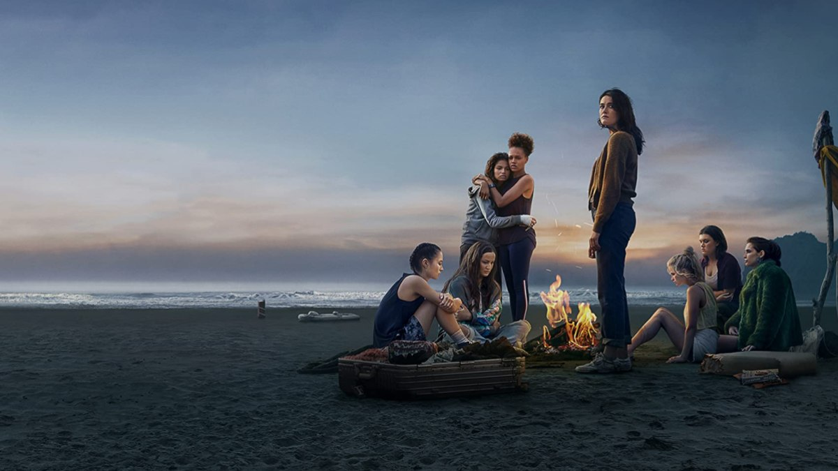 """eight teenage girls stranded on an island looking miserably towards the sunset in """"The Wilds"""""""