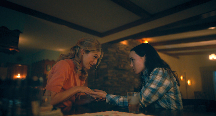 Sissy, a blonde woman in an orange shirt, holds the hands of Vanya (Ellen Page), who is wearing a flannel and looking at her intently. They're in a dark but expansive room lit by numerous candles.