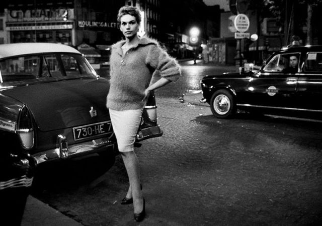 A transgender woman in 1950s/1960s Paris stands in the street at night, her hand on her hip, in a fuzzy sweater and tight pencil skirt. She has her hair pulled back and is wearing a pair of black high heels. It is glamour personified.
