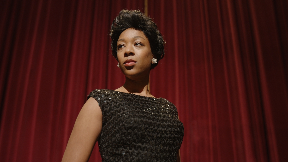 Samira Wiley as Lorraine Hannsberry, wearing a black shimmery dress in front of a red curtain