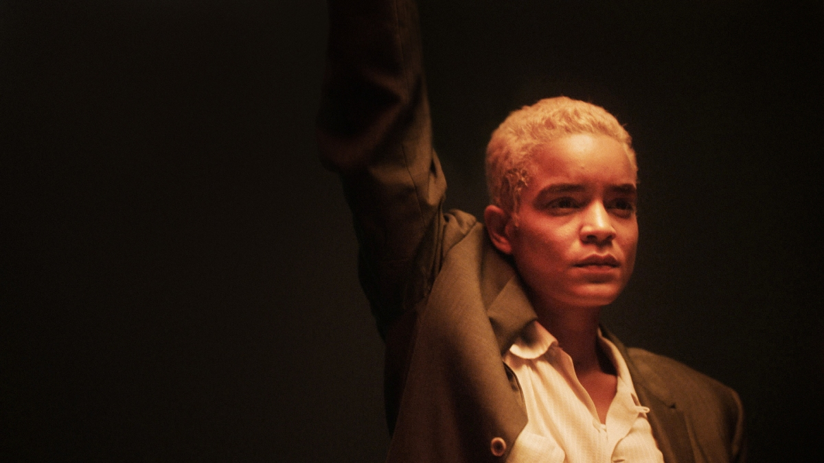Elizabeth Faith Ludlow as Stormé DeLarverie, wearing a suit and shirt with her arm in the air