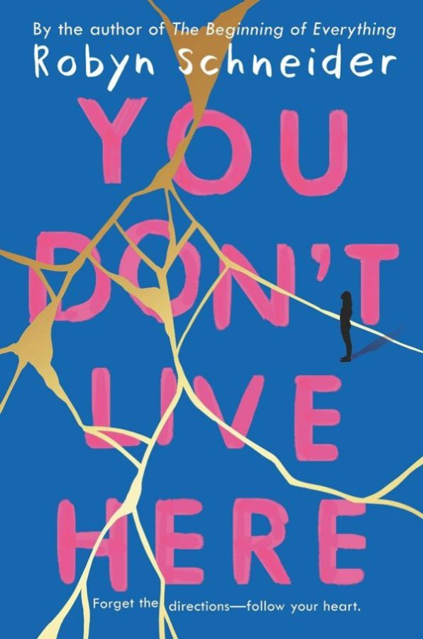 "The cover for ""You Don't Live Here"" is ripped up and put back together like a strewn blue piece of paper being held together with gold tape. The book's title is pink ink, as if it was painted on the tapped up blue paper with a brush."