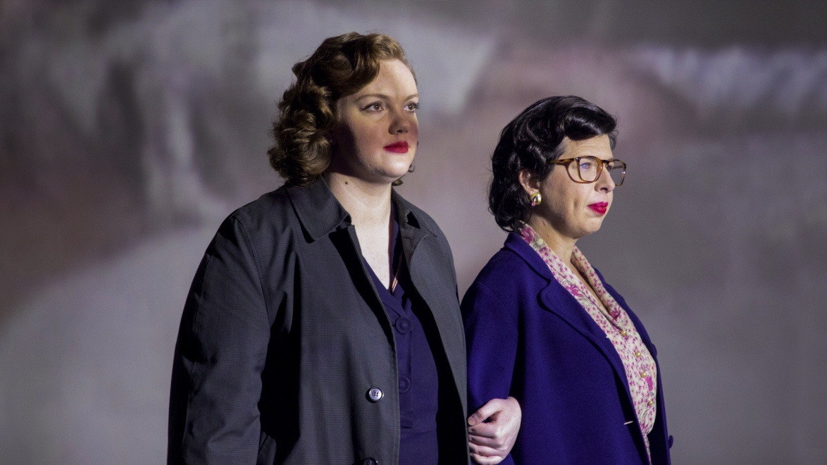 Shannon Purser as Del Martin and Heather Matarazzo as Phyllis Lyon. Arms linked, wearing trench-coats and other '50s-era attire.