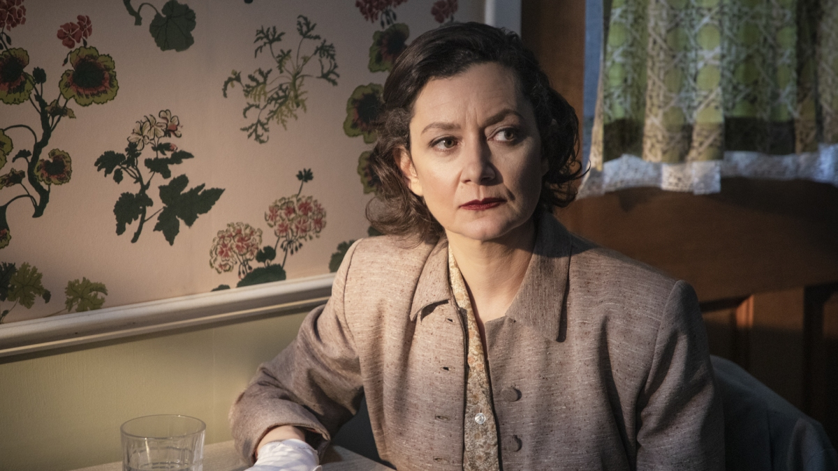 """Sarah Gilbert as """"JM,"""" sitting in her home at a desk, looking uneasy"""