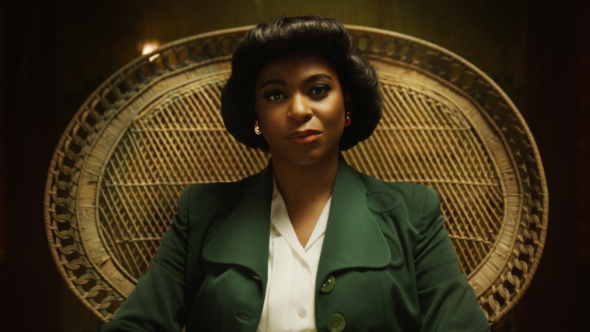 Alexandra Grey as Lucy Hicks Anderson. Wearing a green trenchcoat sitting in a large wicker chair.